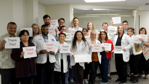 Staff and residents of the UAMS North Street Clinic in Fayetteville, Arkansas, hold up thank you signs.