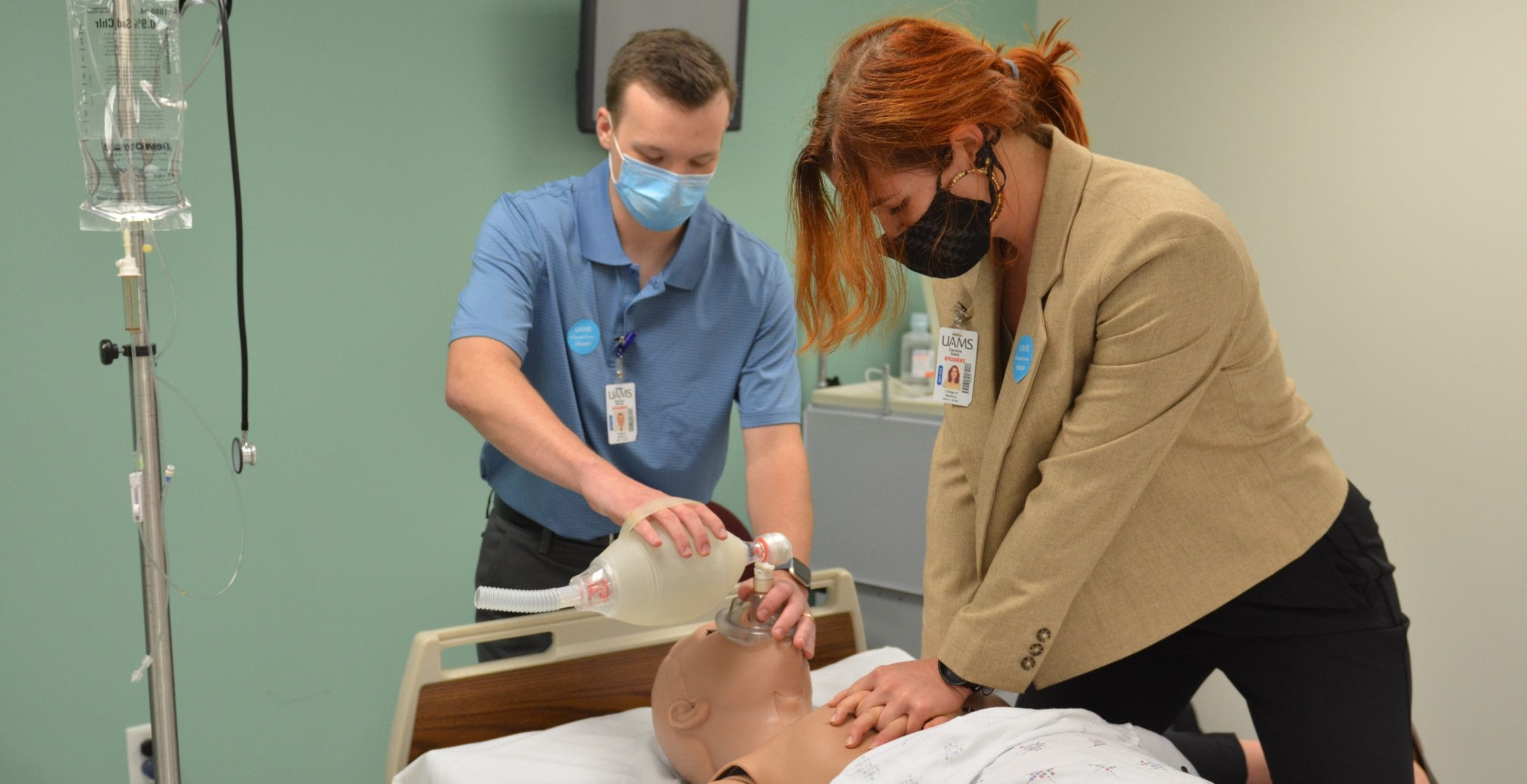 Spencer Parnell and Caroline Geels, first-year students in the College of Medicine's new 3-year M.D. program, practice CPR on a training manikin at the UAMS Northwest Regional Campus in Fayetteville.