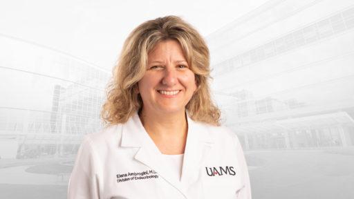 Elena Ambrogini, M.D., Ph. D., in white coat.