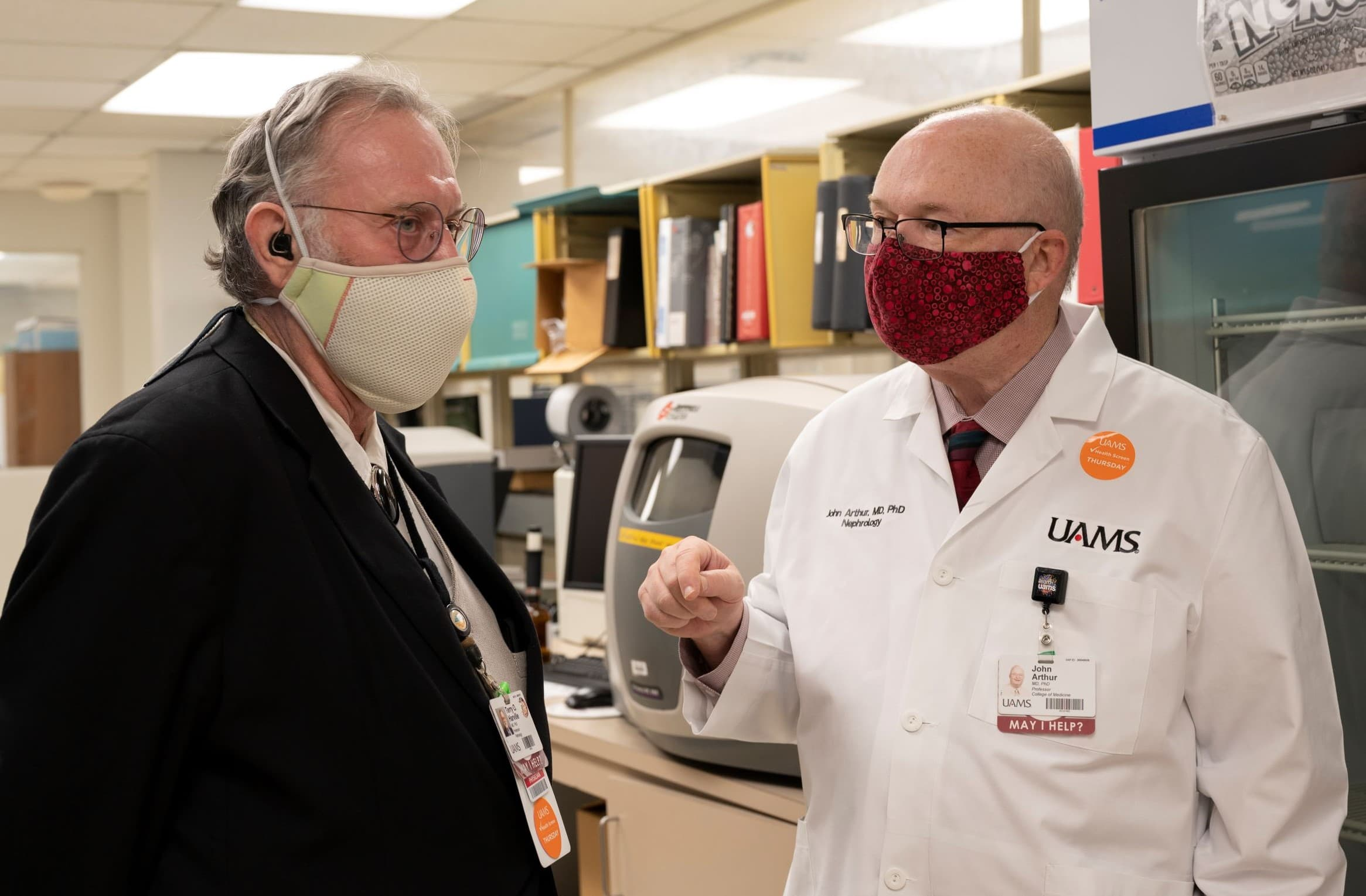 Terry Harville, M.D., Ph.D., consults with John Arthur, M.D., Ph.D., in the UAMS Pathology Lab.