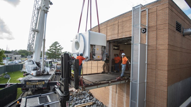 Workers use a crane to hoist and install a new MRI scanner at the UAMS Psychiatric Research Institute
