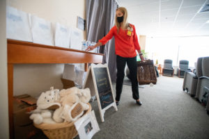 Jennifer Huie, manager of Volunteer Services and the UAMS Hospital Auxiliary, points to baskets of donated plush slippers and skin-care goody bags.