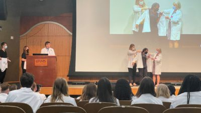 Students walk across the stage one by one to be helped into their white coats