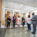 Little Rock Mayor Frank Scott Jr., far right, holds the ribbon as Gloria Richard-Davis, M.D., gets ready to cut it and officially open the the new Culinary Medicine Kitchen at UAMS.