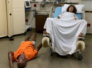 The woman's partner faints as she prepares to deliver in this reenactment.