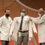 Daniel Acheampong (center) dons his white coat with assistance from Intawat Nookaew, Ph.D., and Cesar M. Compadre, Ph.D.