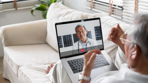 stock image of patient communicating with doctor via laptop from sofa